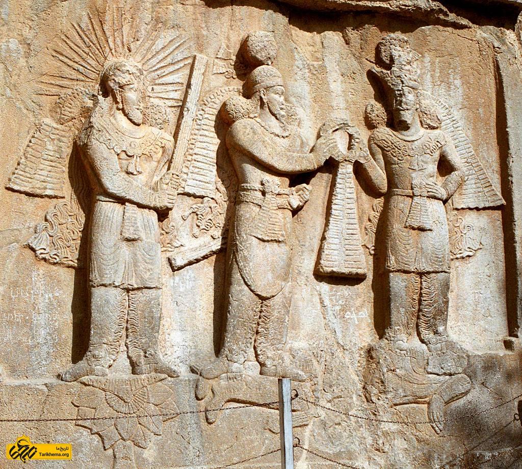 عکس نقشی از تاق بستان در کرمانشاه ایران. در این نقش شاه ساسانی شاپور دوم در میان و در سمت چپ وی اهورا مزدا که حلقه فرایزدی را برای تاجگذاری به او میدهد، بر روی دشمنی به خاک افتاده (ژولیان امپراتور روم) ایستادهاند. درسمت راست شاه، میترا یا مهر، که پیکانهای نوری همچون خورشید از سر او در همهٔ سمتها پراکنده شده، شاخهای از گیاهان به نام «برسم» را در دست گرفتهاست و بر روی گل نیلوفری ایستادهاست.[۱] %d9%85%db%8c%d8%aa%d8%b1%d8%a7-%d8%af%d8%b1-%d8%b2%d9%85%d8%a7%d9%86-%d8%a7%d8%b4%da%a9%d8%a7%d9%86%db%8c%d8%a7%d9%86 Tarikhema.org